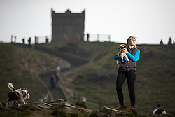 © Licensed to London News Pictures . 18/04/2019. Bolton , UK . Leader of Horwich and Blackrod First Independents MARIE BRADY (58) , from Horwich , (with dog Coco) in front of Rivington Pike on Winter Hill . Independent political parties , not tied to existing national parties , are competing for council seats in wards across the North West . Photo credit : Joel Goodman/LNP