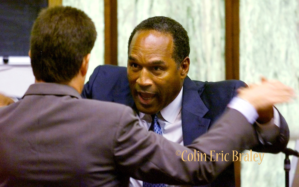 """During his trial, O.J. Simpson (R) demonstrates how he used self defense to push away a man that he had a confrontation with during a """"road rage"""" incident in Miami, Florida in December of 2001. Simpson is accused of assaulting the individual."""