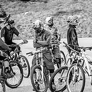 Riders prep their bikes to drop into the Fuzzy Bunny Trail off of Teton Pass near Wilson, Wyoming.