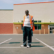 Reverend Chester Williams stands in the parking lot of the closed Bottom Dollar store, which was the only grocery store in the Chew-Belfield neighborhood. Williams has been persistently reaching out to the new owners of the store, Aldi, to try to get them to reopen the store. May 8, 2015. Photo by Lori Waselchuk