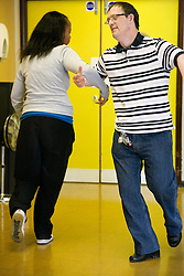 Boyfriend and girlfriend day service users with learning disabilities enjoying a line dancing class,