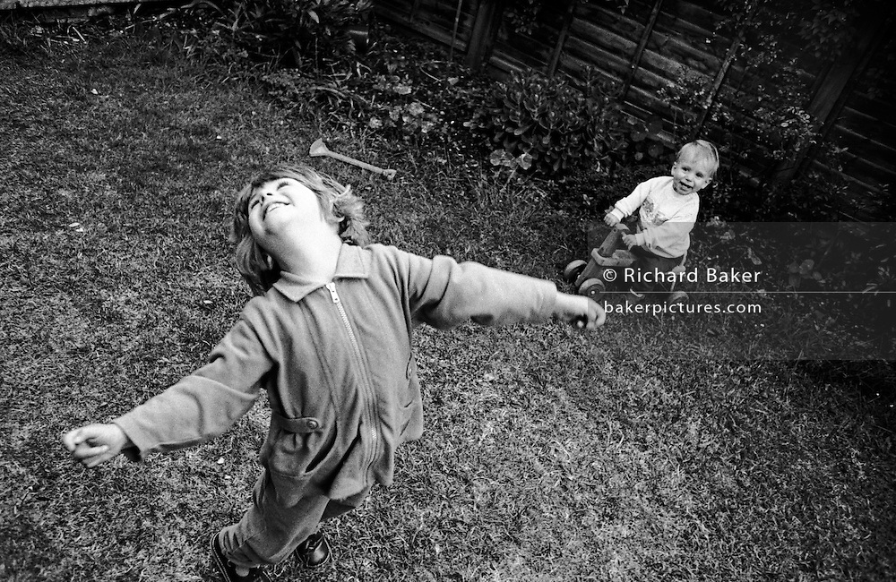 "A three year-old girl throws her head back with joy while playing with her young one-year-old brother in the back garden of their South London home. We look down on the small girl who throws her head back with delight and the freedom of an early summer afternoon at home. Little brother laughs with pleasure too, sitting on a toy tractor. The picture is slanted to lend a sense of drama. From a personal documentary project entitled ""Next of Kin"" about the photographer's two children's early years spent in parallel universes. Model released."