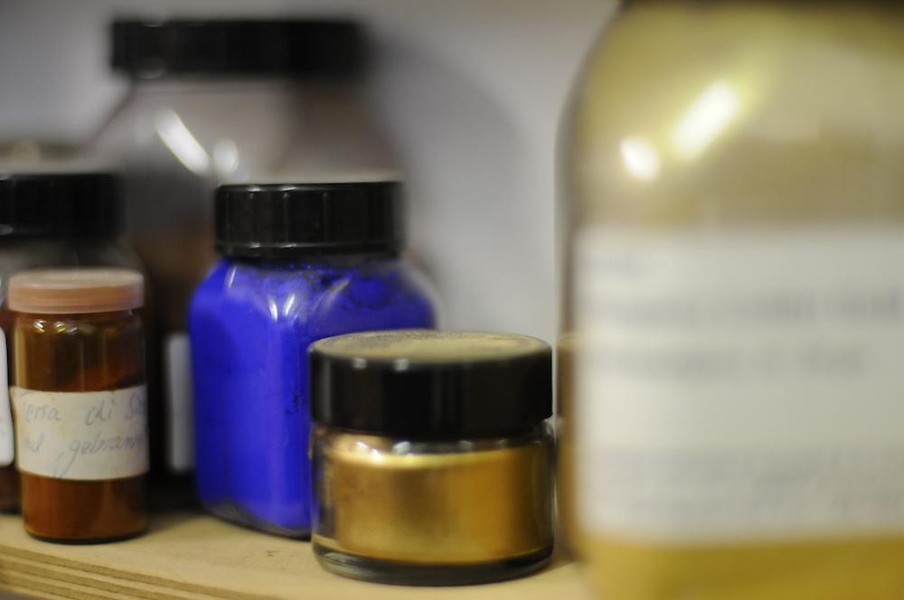 Flaschen und Dosen mit edlen Pigmenten  stehen auf einem  Regal   in einem Studio für Holzrestaurierung   |  |