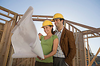 Young couple examining blueprint in construction site