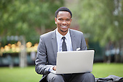 Portrait of a happy African American businessman using laptop in park