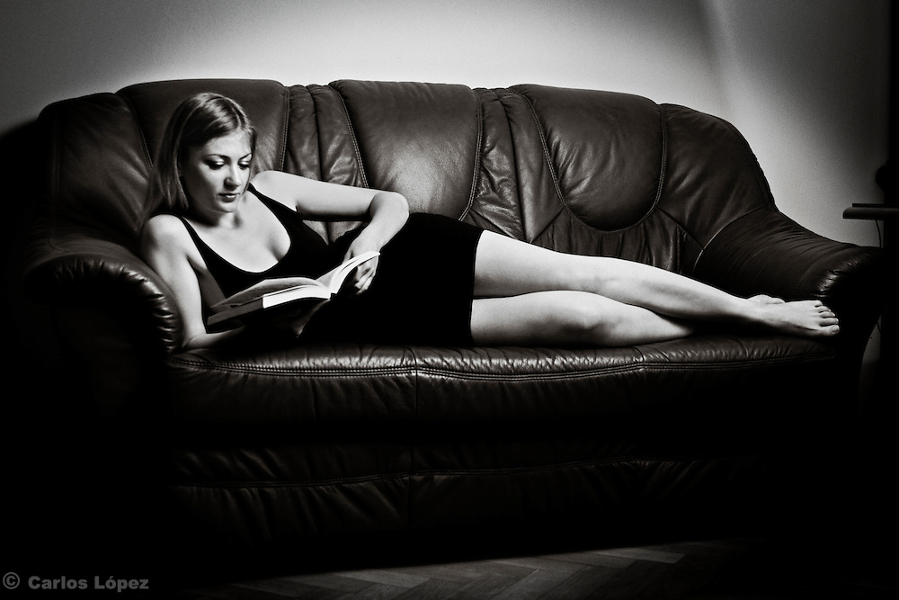 A young woman reading a book lying on a sofa.