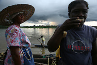 A woman takes a bite of sugar cane as a young boy paddles a canoe by the market dock on the Atrato River in Quibdo, the capital of the state of Choco, on October 6, 2006. Choco is a state that has suffered terribly at the hands of both rightwing paramilitaries and leftist rebels over the years, causing many to flee to other parts of Colombia. The Choco is located on the Pacific coast of Colombia and most of the people are black descendants of African slaves. (Photo/Scott Dalton).