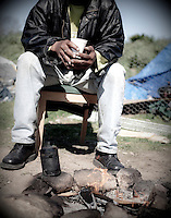"""Robert Burgins sits by his campfire out side his tent that is his home at a homeless encampment or """"tent city"""" on the banks of the American River in Sacramento, CA."""