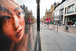 Glasgow, Scotland, UK. 1 April, 2020. Effects of Coronavirus lockdown on streets of Glasgow, Scotland. Photo of model in Victoria's Secret shop looks out on a deserted Buchanan Street with a lone Deliveroo cyclist riding past .Iain Masterton/Alamy Live News