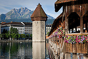 Flowers decorate the Chapel Bridge, set in Lucerne beneath Mount Pilatus, Switzerland.