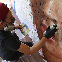 """Ryan """"Arcy"""" Christenson of Connecticut, spray paints a mural of Elvis on the wall of Reed's Saturday for Elvisfest"""