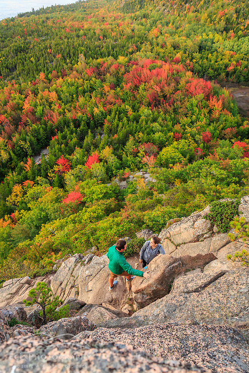 """A young couple hiking """"The Beehive"""" in fall in Maine's Acadia National Park."""