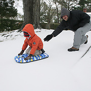 John Helms pushes his son William Helms, 5, on Larchmont Drive in Wilmington, N.C. Wednesday January 29, 2014. Wilmington saw a wintry mix of sleet, snow, and freezing rain Tuesday and Wednesday which caused extensive closings throughout the area. (Jason A. Frizzelle)