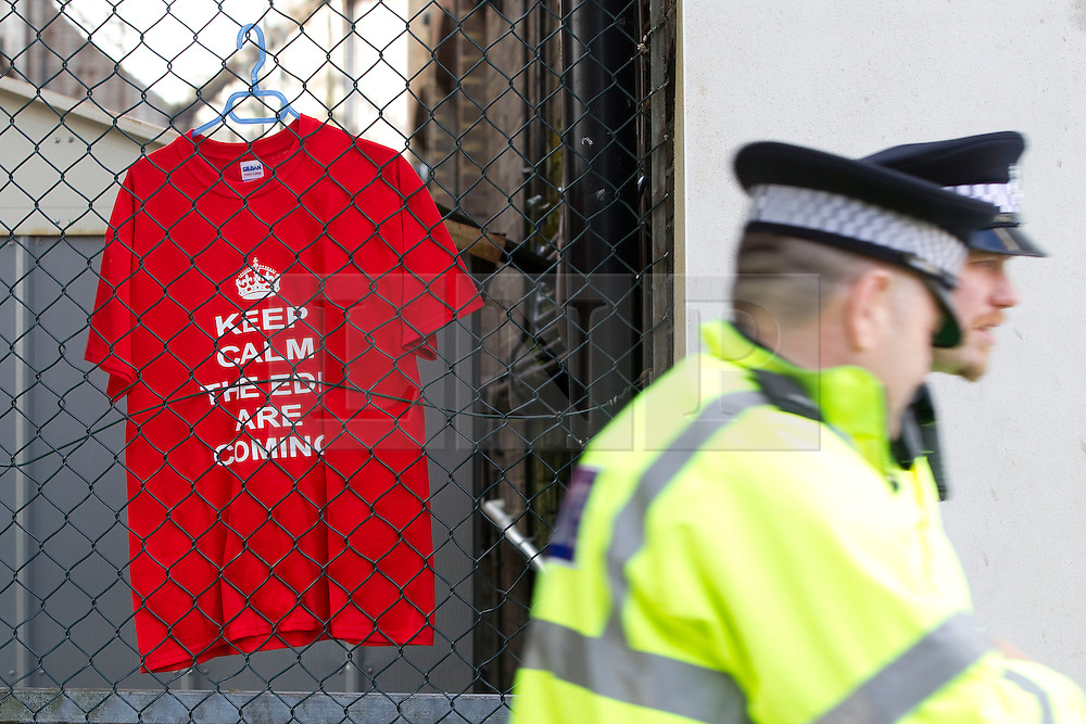 "© Licensed to London News Pictures. 05/05/2012. Luton, UK. Police walk by an EDL sales stall with a t-shirt that reads ""Keep calm the EDL are coming"". The EDL hold a march and demonstration in Luton town centre. About 1500 EDL supporters attended and about 1200 police. A counter protest was also held. Photo credit : Joel Goodman/LNP"