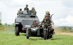 A re-enactors from the Northern World War Two Association Living History group mounted on a German  Sd Kfz 251 Ausf C Half track and BMW R71 motorcycle and sidecar during a large scale battle re-enactment..SPAM 1940's Weekend. Heckmonwyke near Wakefield 10 July 2010 .Images © Paul David Drabble.