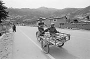 Man driving cart with boy, Peru, 2003