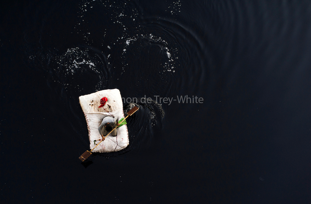 1st December 2014, New Delhi, India. A boy paddles a raft on the Yamuna River in New Delhi, India on the 1st December 2014<br /> <br /> People eke out a living on the Yamuna River by searching for coins and items they can sell that are thrown into the river by Hindus as offerings<br /> <br /> PHOTOGRAPH BY AND COPYRIGHT OF SIMON DE TREY-WHITE<br /> <br /> + 91 98103 99809<br /> email: simon@simondetreywhite.com<br /> photographer in delhi