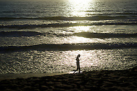 Silhouetted woman walking on a beach at sunset.