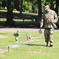 Staff Sgt. David Fetterman looks for the next veteran grace as he and other from the 834th Aviation Support Battallion help place American flags at Tupelo Memorial Park.