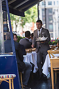 A waiter carries a tray of drinks to a table at George, a private members club in Mayfair, London, United Kingdom.  Mayfair is a very affluent area of London  famous for its exclusive venues and private members clubs.