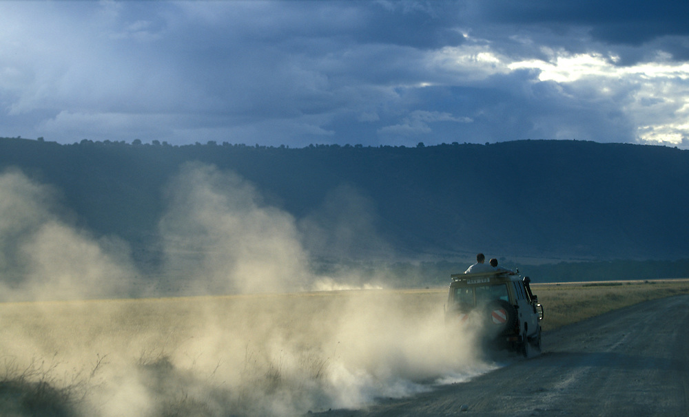 Africa, Tanzania, Ngorongoro Conservation Area, Safari truck sends up cloud of dusk on dirt road inside Ngorongoro Crater