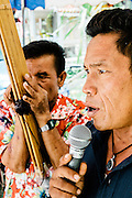 Man singing traditional songs accompanied by Khaen at Temple fair outside of Kumphawapi village, Udon Thani