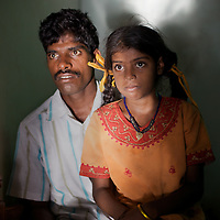 "Viswanathan with his daughter Vijyashree at home in the fishing village of Thazanguda, near Cuddalore. ..Vijita (age 14) and Vijyashree (age 11) Viswanathan lost their mother and brother to the tsunami in 2004. They continue to live in the fishing village of Thazanguda with their father Viswanathan, his second wife Kayalvizhi and their two children Sanjay (age 3) and Monica (age 1). ..Until the beginning of the 2009 academic year in June, Vijita and Vijyashree attended the local Thazanguda school. This village school teaches pupils only until the 8th Standard and with Vijita now entering the 9th, it was decided that the two daughters remain together and both travel 3km to the local town school: the Government Girls High School, Venugopalapuram in Cuddalore. ..At the same time Viswanathan decided he would cease day-to-day care of his daughters and place them in the Government Home for Tsunami Children, also in Cuddalore. This was not a move welcomed by either Vijita or Vijyashree and one afternoon after just two weeks at the orphanage, the two girls ran away. At roll call in the orphanage that evening the alarm was sounded and the two sisters were eventually located in Thazanguda waiting for their father and Kayalvizhi who were both away at the time. Realising his daughters' unhappiness, Viswanathan then took them out of the Government home. ..According to her class teacher, Vijita often compares her step-mother to her mother and concludes that she wants her mother back. Vijita confides in her teachers that her stepmother is forever demanding that she and her sister Vijyashree undertake housework. This frustration at home is tempered by the genuine love both sisters have for their father and two younger siblings Sanjay and Monica. Vijita expresses a lonelyness without her mother. Pushpavalli concludes that ""Vijita wants something else beyond the love of her father and sister"". ..Viswanathan appears genuinely to want the best for his two elder daughters. His experimen"