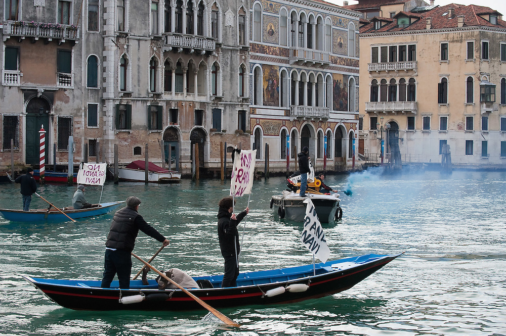 "VENICE, ITALY - JANUARY 16:  Protesters block the Grand Canal  while holding several banners reading ""Stop the large Ships""  on the day of the special meeting discussing the environmental impact of cruises in St Mark's basin on January 16, 2012 in Venice, Italy. Protest are mounting in Venice against large cruise ships crossing St Marks's basin after the Costa Concordia tragedy.."