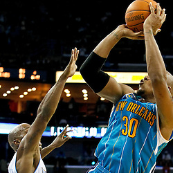 October 29, 2010; New Orleans, LA, USA; New Orleans Hornets power forward David West (30) shoots over Denver Nuggets point guard Chauncey Billups (1) during the fourth quarter at the New Orleans Arena. The Hornets defeated the Nuggets 101-95.  Mandatory Credit: Derick E. Hingle