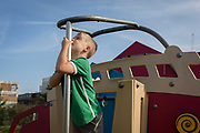 A three year-old boy explores a playpark climbing frame, on 25th August, in Ruskin Park, London borough of Lambeth, England.