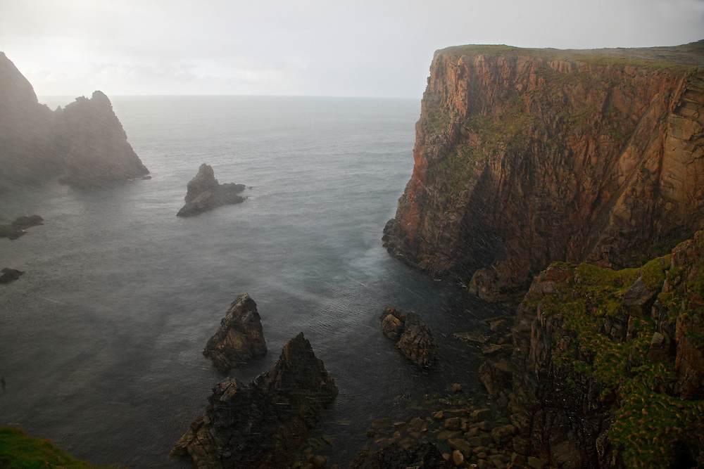 Heavy rainshower  at rugged coast, Tory Island, North-Western Ireland