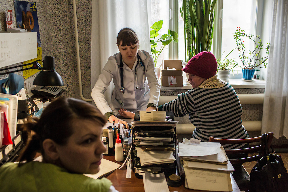ZIMOGORYE, UKRAINE - MARCH 15, 2015: Yelena Beybudova, left, a nurse, and Yevgeniya Kovalenko, a general practitioner, center, consult with a patient at the Zimogoryivskaya Ambulatory in Zimogorye, Ukraine. CREDIT: Brendan Hoffman for The New York Times