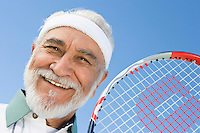 Senior man holding tennis racket, portrait