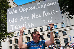 London, August 23rd 2014. A protester's banner makes the distinction between perceived injustices carried out by the state of Israel and anti-Semitism, as  protesters outside Downing Street demand that Britain stops arming Israel.