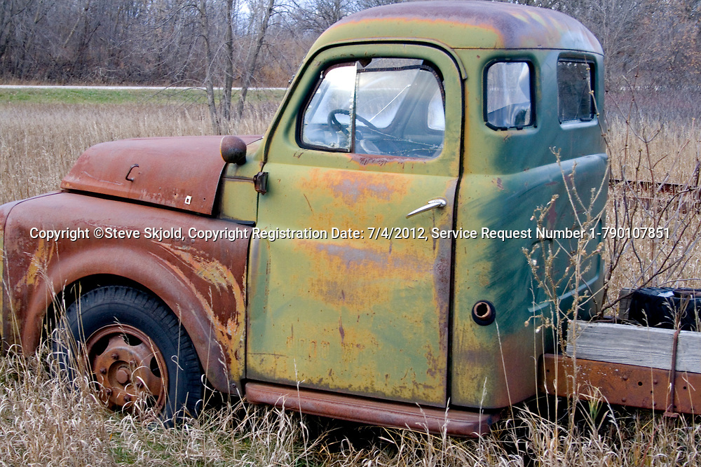 Green truck cab with rusted hood forgotten in a farmer's field. Ottertail Minnesota MN USA