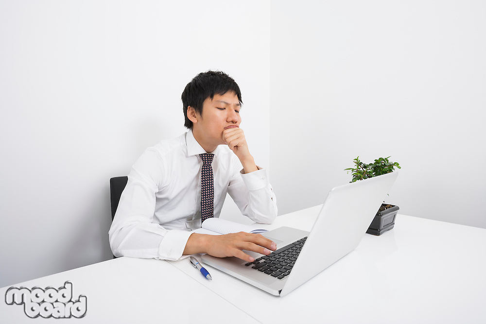 Bored mid adult businessman using laptop at desk in office
