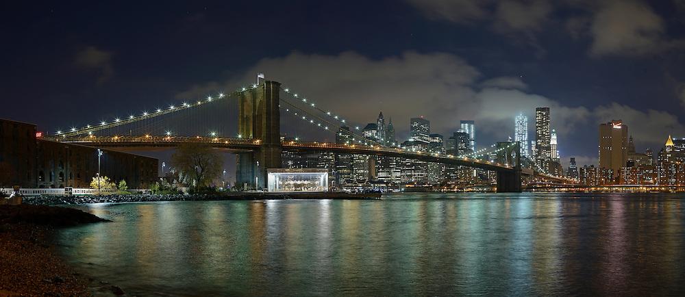 Brooklyn Bridge East River and Manhattan at night.