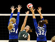 Perryville's Natalie Bauwens hits the ball as Notre Dame's Kate Edwards, left, and Amy Wibbenmeyer, right, block during the second game of a Class 3 District 1 title match on Tuesday, Oct. 26, 2010, at Dexter. Notre Dame won 2-0.