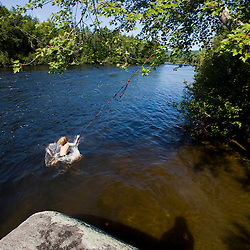 A boy plays on a rope swing at Mollidgewock State Park in Errol, New Hampshire. Androscoggin River.