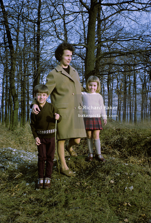 A 1960s mother stands for a family picture in woodland with her 5 year-old son and 4 year-old daughter