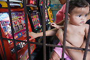 08 JANUARY 2007 - MANAGUA, NICARAGUA:  A woman plays slot machines in a stall in the Mercado Oriental, the main market that serves Managua, Nicaragua. The market encompasses dozens of square blocks and is the largest market in Central America. The Nicaraguan government legalized gambling in the early 1990's and small shops with slot machines are common in the markets.   PHOTO BY JACK KURTZ