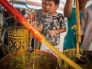"""21 JULY 2013 - BANGKOK, THAILAND:  People pour molten wax into candle molds to make merit at Wat Mahabut on the first day of Vassa, the three-month annual retreat observed by Theravada monks and nuns. The candles are then presented to the temple. Now monks rely on electric lights, but traditionally the temples relied on candles provided by the community. On the first day of Vassa (or Buddhist Lent) many Buddhists visit their temples to """"make merit."""" During Vassa, monks and nuns remain inside monasteries and temple grounds, devoting their time to intensive meditation and study. Laypeople support the monastic sangha by bringing food, candles and other offerings to temples. Laypeople also often observe Vassa by giving up something, such as smoking or eating meat. For this reason, westerners sometimes call Vassa the """"Buddhist Lent.""""       PHOTO BY JACK KURTZ"""