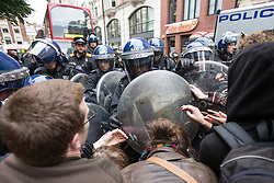 © Licensed to London News Pictures . 11/06/2013 . London , UK . Police push back anti-capitalist protesters in Golden Square , Soho after an injured man was seen being wheeled on to an ambulance adjacent to Beak Street where police detained dozens of protesters who had occupied an empty police station today (Tuesday 11th June) . Demonstrations in London today (Tuesday 11th June 2013) ahead of Britain hosting the 39th G8 summit on 17th/18th June at the Lough Erne Resort , County Fermanagh , Northern Ireland , next week . Photo credit : Joel Goodman/LNP