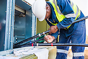 Electrician connecting the electric cable info the substation