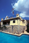 A girl jumping off the roof of a house into a swimming pool, Ibiza, 2000's
