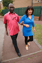 Elderly black man with white woman carer walking