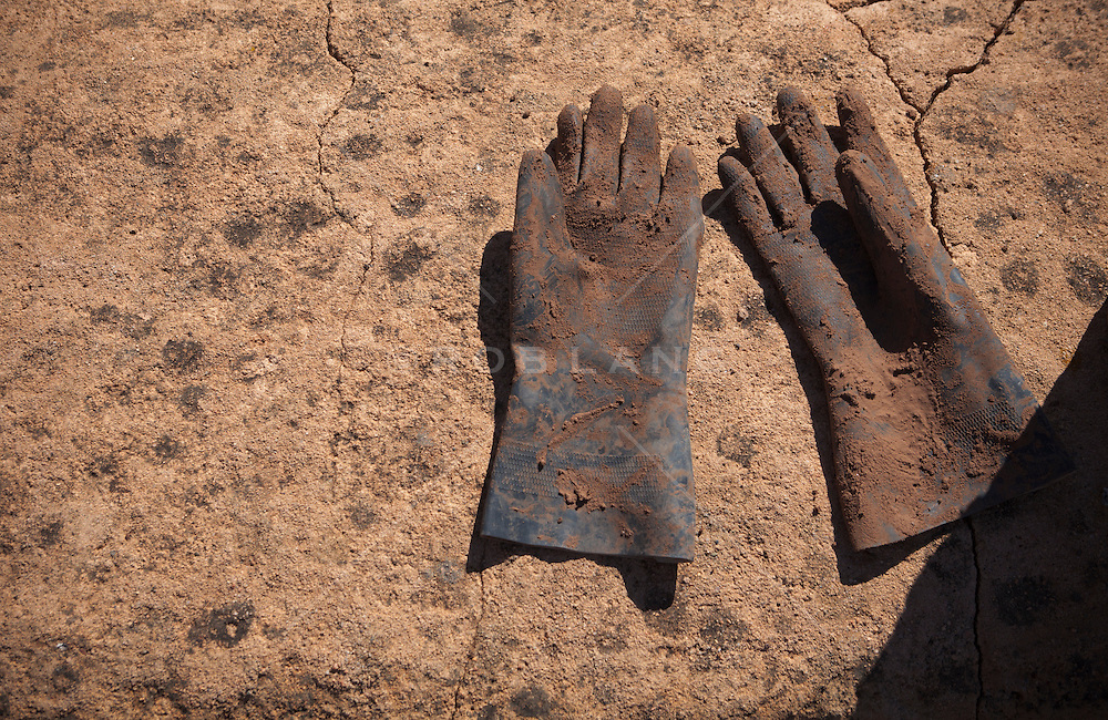 work gloves on a dry adobe building