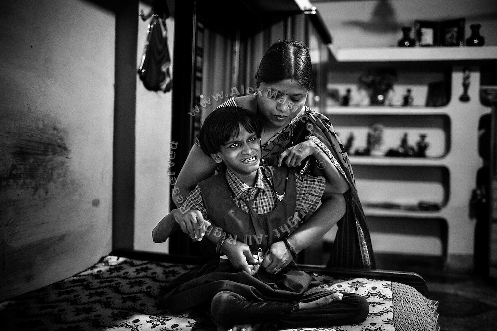 Before attending Chingari Trust Rehabilitation Centre, Rupa Raiqwa, 44, is tying the belt of her disabled daughter Sanjena, 11, a girl affected by severe cerebral palsy, while inside their home in Chola, one of the water-affected colonies near Bhopal, Madhya Pradesh, central India, near the abandoned Union Carbide (now DOW Chemical) industrial complex. Sanjena's father, 44, is a '1984 Gas Survivor'.