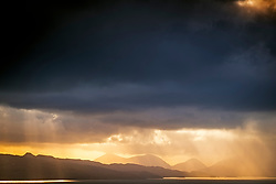 Light filters through a rainstorm above the Isle of Skye.