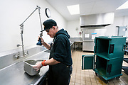 Bret Kuhn washes off serving dishes in the wash room at Union South in Madison, WI on Tuesday, April 30, 2019.